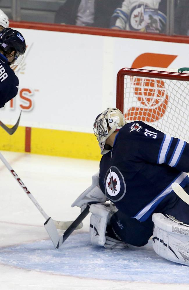 Montreal Canadiens' Brandon Prust (8) scores on Winnipeg Jets' goaltender Ondrej Pavelec (31) as Jets's Jacob Trouba (8) trying to clear him away during the first period of an NHL hockey game in Winnipeg, Manitoba, Tuesday, Oct. 15, 2013