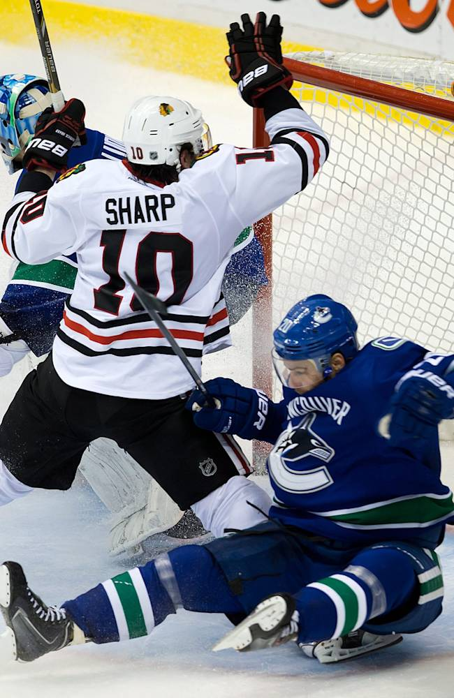 Chicago Blackhawks' Patrick Sharp, center, and Vancouver Canucks' Chris Higgins, right, collide in front of goalie Roberto Luongo during third period NHL hockey action in Vancouver, British Columbia Saturday Nov. 23, 2013