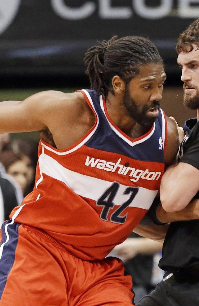 Minnesota Timberwolves' Kevin Love, right, slows Washington Wizards' Nene Hilario on a drive during the first quarter of an NBA basketball game, Friday, Dec. 27, 2013, in Minneapolis