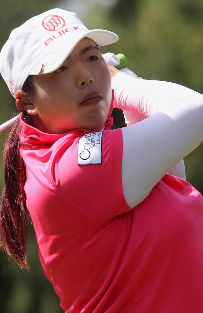 Shanshan Feng, of China, watches her tee shot on the 14th hole at the Canadian Pacific Women's Open golf tournament in London, Ontario, Thursday, Aug. 21, 2014