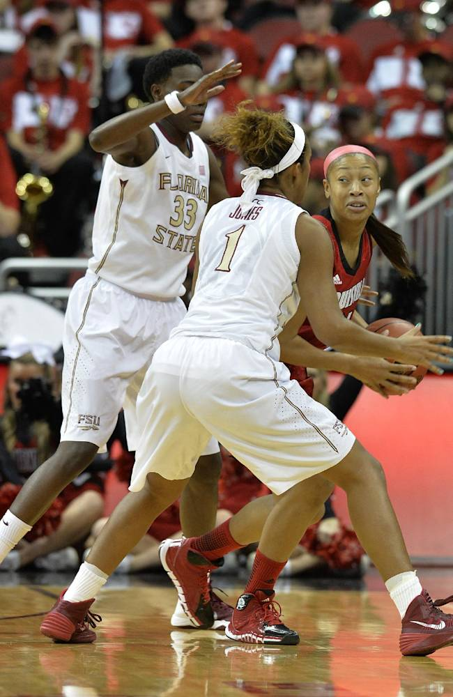 Louisville's Antonita Slaughter, right, looks for help from the defense of Florida State's Natasha Howard, left and Morgan Jones during the first half of their NCAA college basketball game onSunday Nov. 24, 2013, in Louisville, Ky