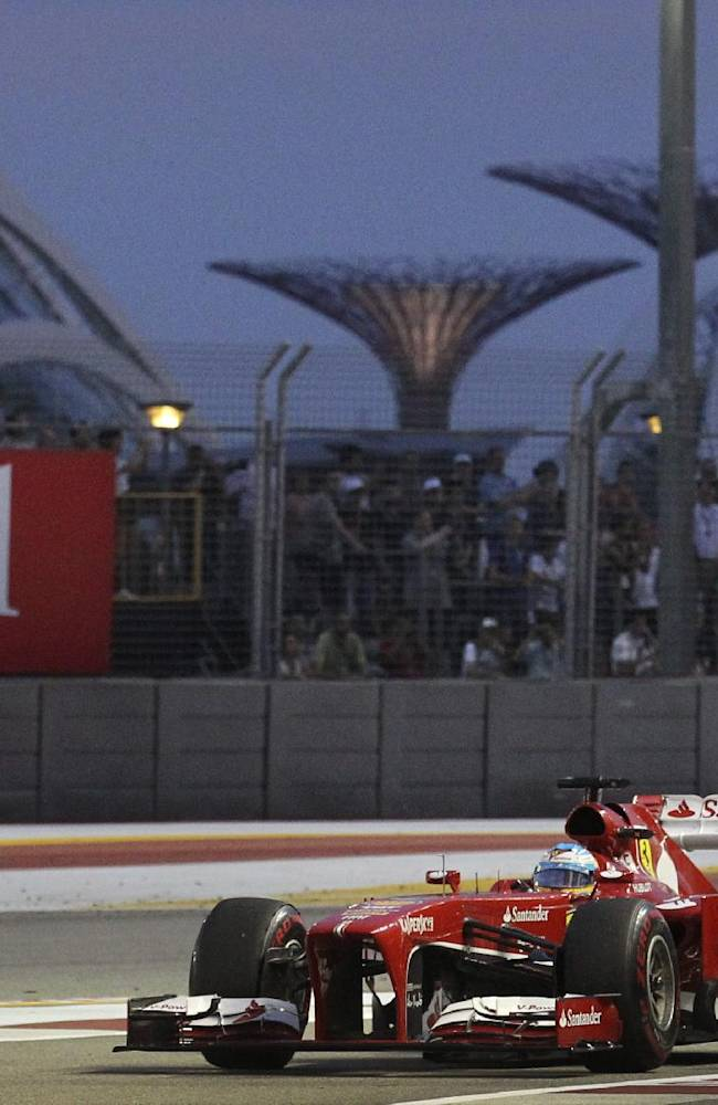 Ferrari driver Fernando Alonso of Spain steers his car back into the pit during the third practice session of the Singapore Formula One Grand Prix on the Marina Bay City Circuit in Singapore, Saturday, Sept. 21, 2013