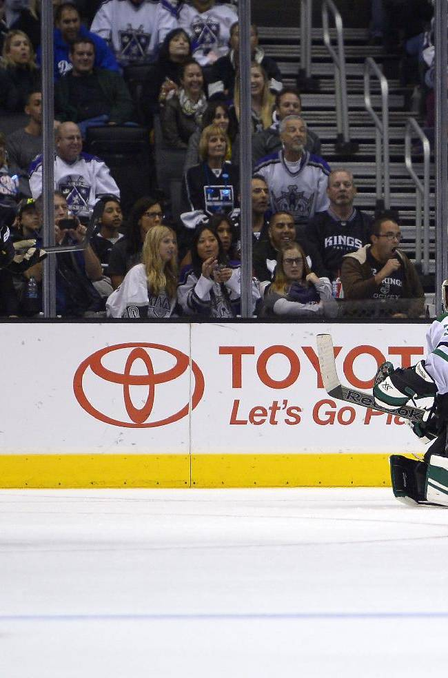 Los Angeles Kings left wing Kyle Clifford, center, jumps as he scores on Dallas Stars goalie Dan Ellis, right, as defenseman Sergei Gonchar, of Russia, looks on during the third period of their NHL hockey game, Saturday, Oct. 19, 2013, in Los Angeles. The Kings won 5-2
