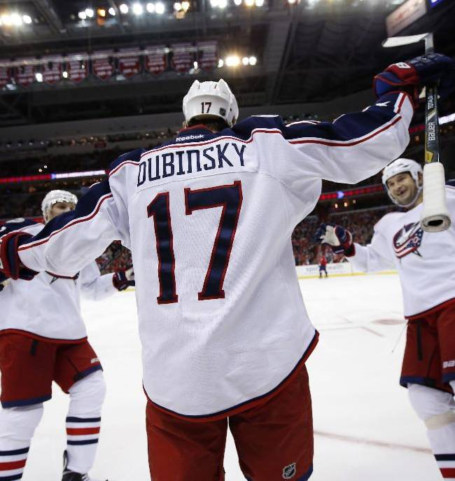 Columbus Blue Jackets defenseman Jack Johnson, left, center Brandon Dubinsky (17) and defenseman Fedor Tyutin, of Russia, celebrate Dubinsky's goal in the second period of an NHL hockey game against the Washington Capitals, Tuesday, Nov. 12, 2013, in Washington