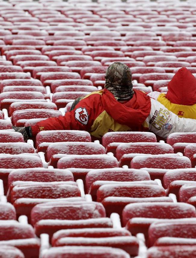 Fans sit in snowy seats at Arrowhead Stadium as they wait for the start of an NFL football game between the Kansas City Chiefs and the Indianapolis Colts Sunday, Dec. 22, 2013, in Kansas City, Mo