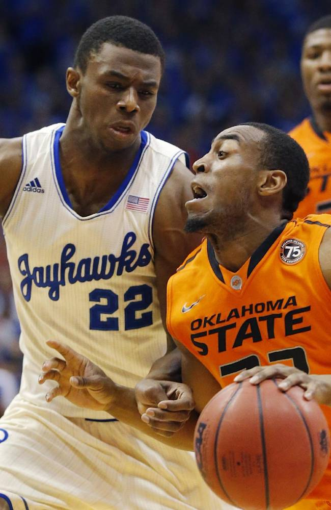 Oklahoma State guard Markel Brown, right, is fouled by Kansas guard Andrew Wiggins (22) during the second half of an NCAA college basketball game at Allen Fieldhouse in Lawrence, Kan., Saturday, Jan. 18, 2014. Kansas defeated Oklahoma State 80-78