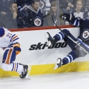 Winnipeg Jets' Blake Wheeler (26) gets dumped by Edmonton Oilers' Andrew Ference (21) during third period NHL action in Winnipeg, Manitoba, on Wednesday, Dec. 3, 2014 The Associated Press