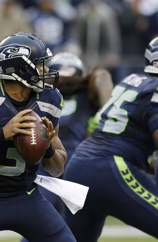 Seattle Seahawks quarterback Russell Wilson, left, drops to pass against the San Francisco 49ers in the first half of an NFL football game, Sunday, Sept. 15, 2013, in Seattle