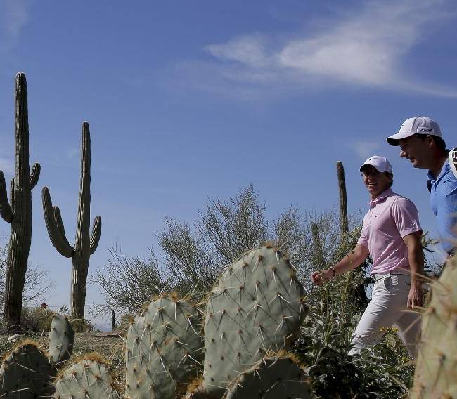 CORRECTS NAME OF CADDIE TO JP FITZGERALD, INSTEAD OF DAVE RENWICK - Rory McIlroy, left, walks off the 17th tee with his caddie, JP Fitzgerald, during a practice round for the Match Play Championship golf tournament Tuesday, Feb. 18, 2014, in Marana, Ariz