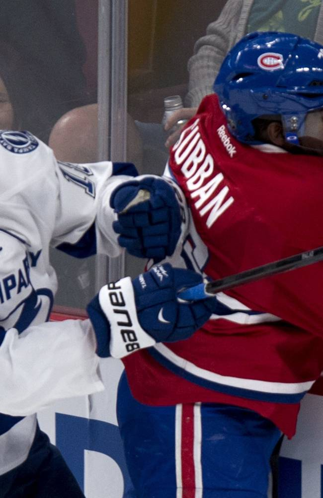 Montreal Canadiens' P.K. Subban is checked into the boards by Tampa Bay Lightning's Ondrej Palat during the first period of an NHL hockey game Tuesday, Nov. 12, 2013, in Montreal