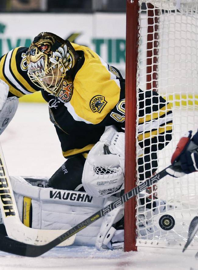 Washington Capitals center Jay Beagle, right, tries to knock the puck ahead into the crease as Boston Bruins goalie Tuukka Rask, of Finland, drops to the ice during the third period of an NHL preseason hockey game, Monday, Sept. 23, 2013, in Boston.  The Bruins won 3-2 in overtime
