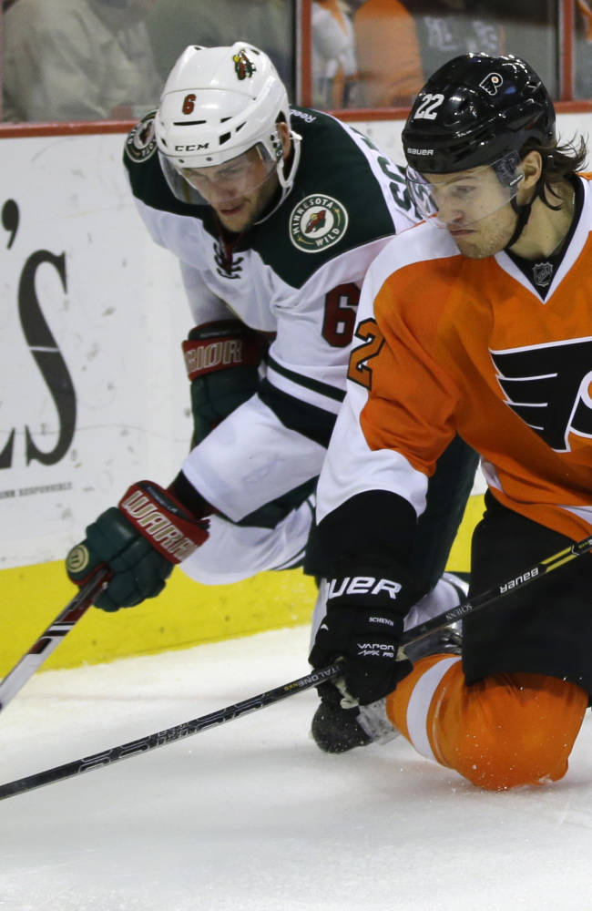 Philadelphia Flyers' Luke Schenn, right, and Minnesota Wild's Marco Scandella chase down a loose puck during the third period of an NHL hockey game, Monday, Dec. 23, 2013, in Philadelphia. Philadelphia won 4-1