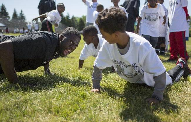 Draymond Green motivates children to do push-ups at LaMarr Woodley's football camp held at Saginaw High School, Saturday, June 14, 2014
