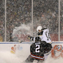 Chicago Blackhawks defenseman Duncan Keith (2) and Pittsburgh Penguins left wing Chris Kunitz (14) kick up snow and ice as they vie for a loose puck during the first period of an NHL Stadium Series hockey game at Soldier Field on Saturday, March 1, 2014,