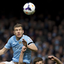 Liverpool's Steven Gerrard, right, fights for the ball against Manchester City's Edin Dzeko during their English Premier League soccer match at Anfield Stadium, Liverpool, England, Sunday April 13, 2014