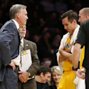 Los Angeles Lakers' Steve Nash looks down while talking with coach Mike D'Antoni, left, as athletic trainer Gary Vitti, left rear, stands with them along with Steve Blake, right, while officials review a call at the end of the first half of an NBA basketb