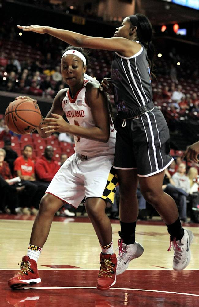 Delaware State's Raven Bankstron, right, defends as Maryland's Lexie Brown drives to the basket in the first half of an NCAA college basketball game, Saturday, Dec. 14, 2013, in College Park, Md