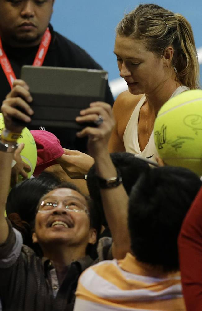 A man takes a 'selfie' as Maria Sharapova of the Manila Mavericks autographs large tennis balls of supporters, following her win over  Kristina Mladenovic of the UAE Royals in their IPTL (International Premier Tennis League) Women's Singles match Friday, Nov. 28, 2014 at the Mall of Asia Arena at suburban Pasay city, south of Manila, Philippines. The IPTL, featuring four teams, introduces a new format in tennis and a chance for a championship prize of $1-million dollars