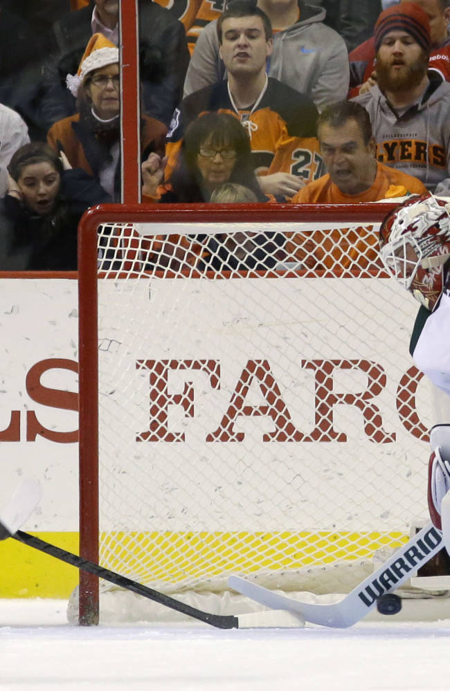 Philadelphia Flyers' Wayne Simmonds, left, scores a goal past Minnesota Wild's Niklas Backstrom, of Finland, during the first period of an NHL hockey game, Monday, Dec. 23, 2013, in Philadelphia