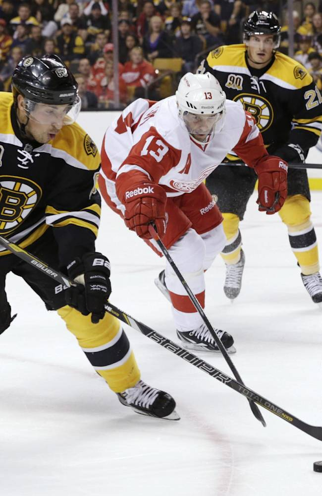 Boston Bruins forward Brad Marchand (63) and Detroit Red Wings' Pavel Datsyuk (13), of Russia, chase the puck during the first period of an NHL hockey game on Saturday Oct. 5, 2013, in Boston