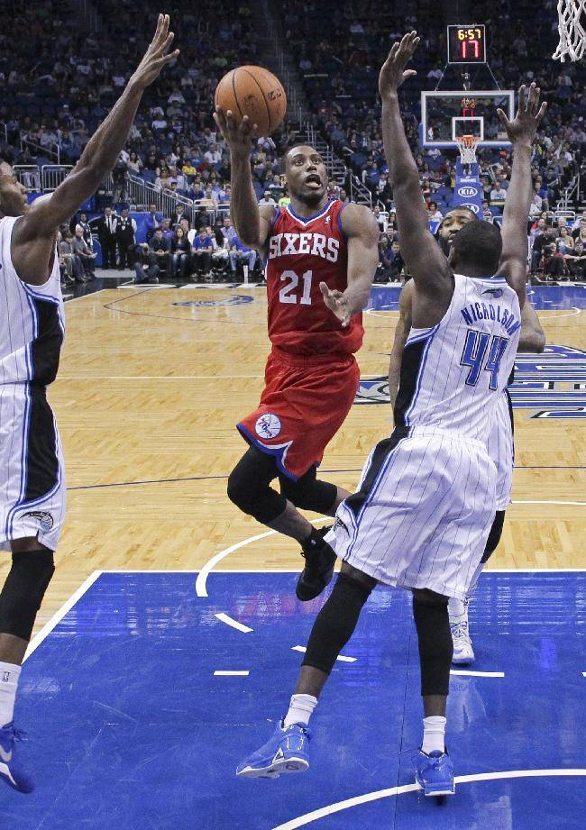 Philadelphia 76ers' Thaddeus Young, center, gets between Orlando Magic's Maurice Harkless, left, and Andrew Nicholson (44) for a shot during the second half of an NBA basketball game in Orlando, Fla., Sunday, March 2, 2014. Orlando won 92-81