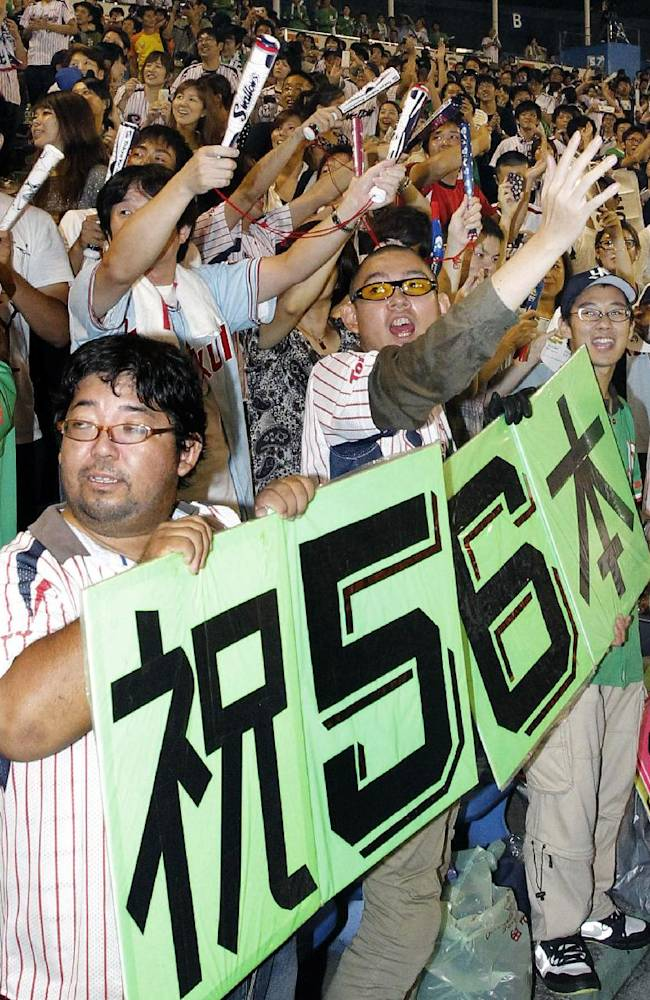 Fans in the stands celebrate after Yakult Swallows' Wladimir Balentien hit his 56th homer off Hanshin Tigers' Daiki Enokida in the first inning of their regular season baseball game at Jingu Stadium in Tokyo Sunday, Sept. 15, 2013. Former major leaguer Balentien broke the Japanese single-season record of 55 set by legendary slugger Sadaharu Oh 49 years ago. The banner held by fans read:
