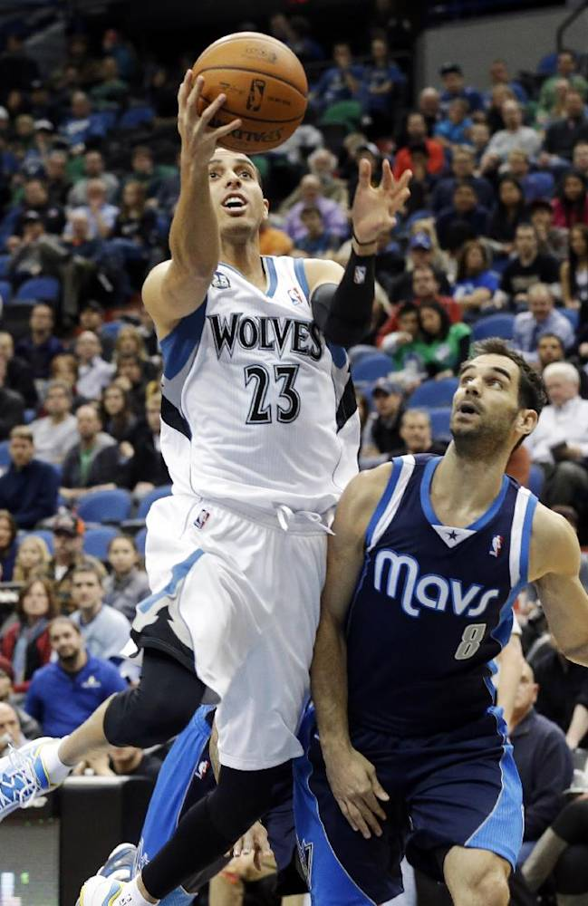 Minnesota Timberwolves' Kevin Martin, left, lays up a shot as Dallas Mavericks' Jose Calderon, of Spain, watches in the first quarter of an NBA basketball game, Monday, Dec. 30, 2013, in Minneapolis