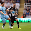 Manchester City's Samir Nasri, left, vies for the ball with Newcastle United's Paul Dummett, right, during their English Premier League soccer match at St James' Park, Newcastle, England, Sunday, Aug. 17, 2014