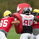 Atlanta Falcons practice squad tight end Kyle Miller, left, defensive end Stansly Maponga, centre, and practice squad running back Jerome Smith block with pads during a training session at the Arsenal FC training ground in London Colney, England, Wednesda
