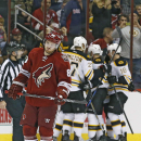 Arizona Coyotes' Mikkel Boedker, left, of Denmark, skates away dejectedly as Boston Bruins' Dougie Hamilton (27), Dennis Seidenberg (44), of Germany, and Reilly Smith (18) celebrate a goal scored by teammate Brad Marchand during the second period of an NH