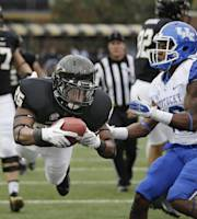 Vanderbilt running back Brian Kimbrow (25) dives over the goal line for a touchdown on a 21-yard run as Kentucky cornerback Cody Quinn, right, arrives too late in the first quarter of an NCAA college football game on Saturday, Nov. 16, 2013, in Nashville, Tenn. (AP Photo/Mark Humphrey)