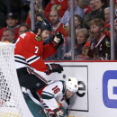 Chicago Blackhawks defenseman Brent Seabrook (7) checks Minnesota Wild left wing Jason Zucker behind the Blackhawks' net during the first period of an NHL hockey game Tuesday, Dec. 16, 2014, in Chicago The Associated Press