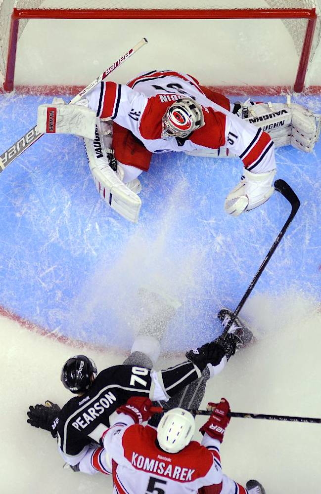 Los Angeles Kings left wing Tanner Pearson, center, tries to get a shot in on Carolina Hurricanes goalie Anton Khudobin, top, of Kazakhstan, as Mike Komisarek defends during the first period of an NHL hockey game, Saturday, March 1, 2014, in Los Angeles