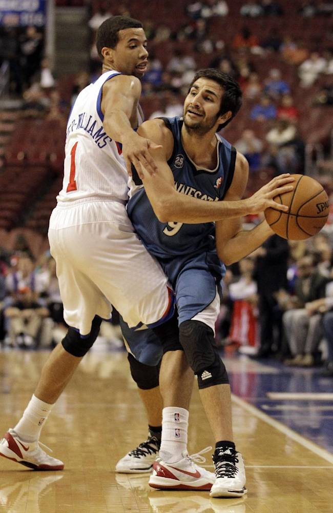 Minnesota Timberwolves' Ricky Rubio, right, passes the ball around Philadelphia 76ers' Michael Carter-Williams in the first half of a preseason NBA basketball game, Wednesday, Oct. 23, 2013, in Philadelphia