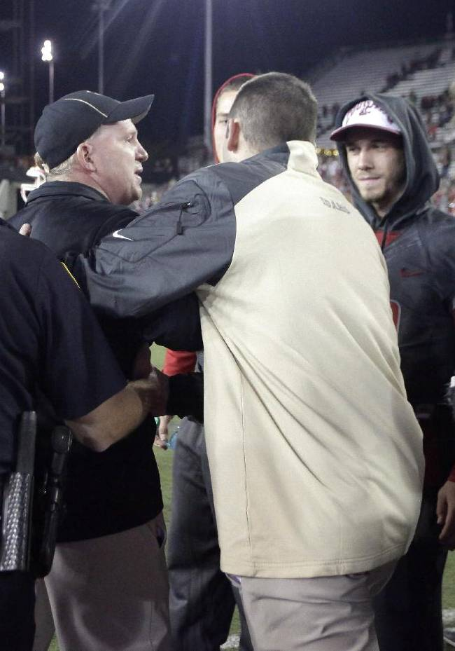Idaho head coach Paul Petrino, second from left, is hustled off-field by a Moscow, Idaho, police officer and an Idaho athletics employee as Washington State players look on after a verbal exchange with Washington State head coach Mike Leach, not seen, after an NCAA college football game Saturday, Sept. 21, 2013, in Pullman, Wash. Washington State won 42-0 in the first meeting between the teams that are only eight miles apart since 2007