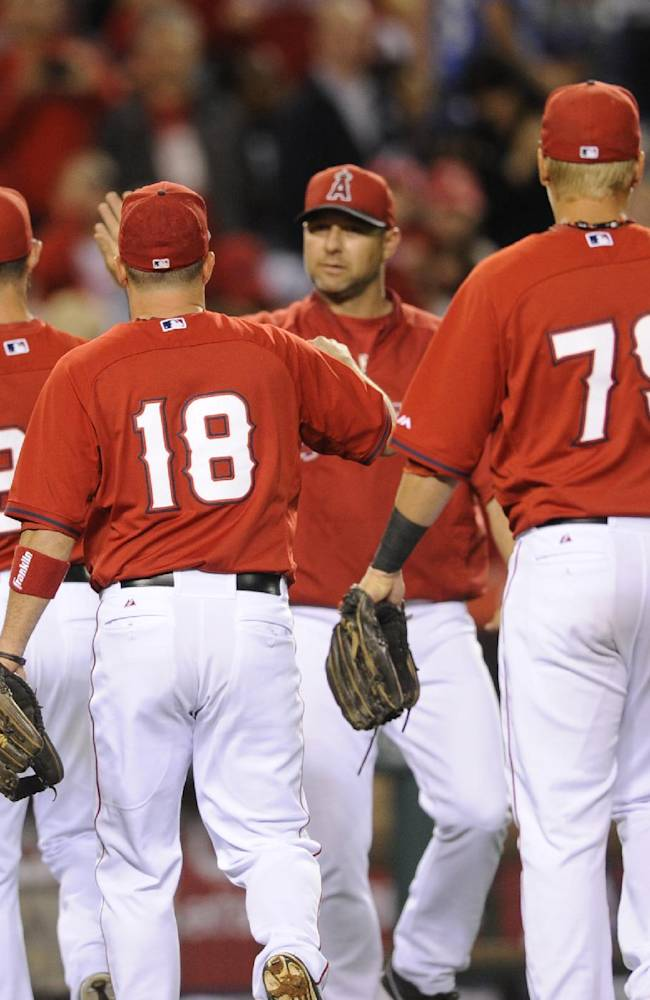 Los Angeles Angels congratulate one another after defeating the Los Angeles Dodgers 6-2 in an exhibition baseball game in Anaheim, Calif., Saturday, March 29, 2014