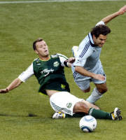 FILE - In this July 2, 2011, file photo, Portland Timbers midfielder Jack Jewsbury, left, and Sporting Kansas City midfielder Graham Zusi battle for the ball during the first half of their MLS soccer game in Portland, Ore. At a chilly morning practice for the Timbers, most of the players are bundled up against the threat of rain, even snow. Not captain Jack Jewsbury. He's out in the 30-degree temperatures in short sleeves and shorts. (AP Photo/Don Ryan, File)