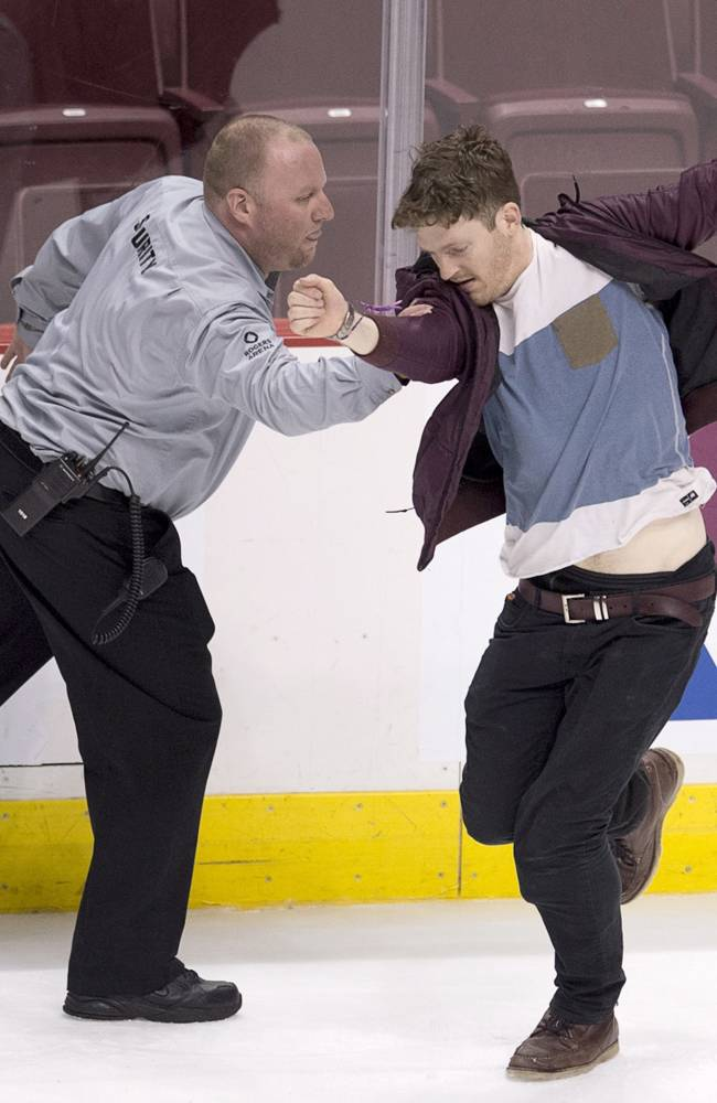 A security guard tries to catch a hockey fan running on the ice following the third period of NHL action against the Vancouver Canucks and the Anaheim Ducks in Vancouver, Monday, April 7, 2014