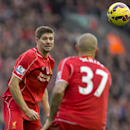 Liverpool's Steven Gerrard, left, passes the ball to teammate Martin Skrtel during the English Premier League soccer match between Liverpool and Chelsea at Anfield Stadium, Liverpool, England, Saturday, Nov. 8, 2014