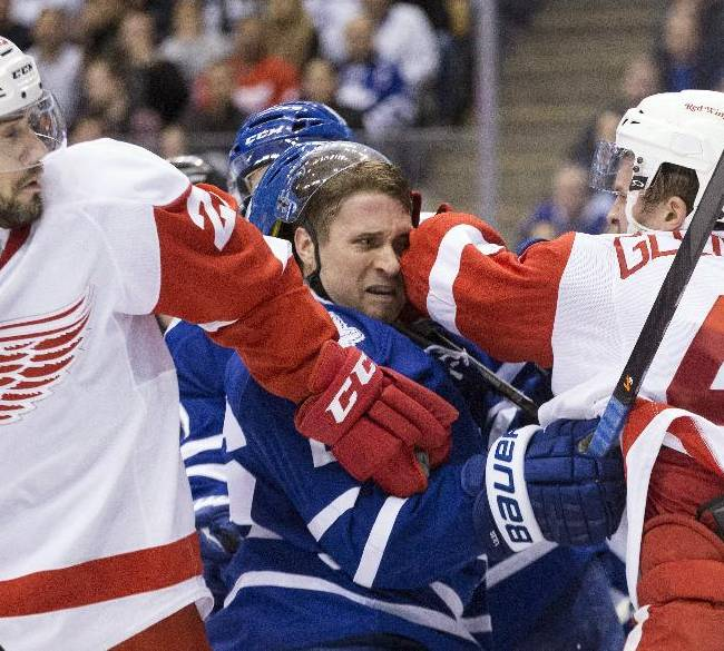 Toronto Maple Leafs' John-Michael Liles, center, tangles with Detroit Red Wings' Luke Glendening, right, as Detroit's Drew Miller skates in during the third period of an NHL hockey game in Toronto on Saturday, Dec. 21, 2013
