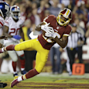 Washington Redskins wide receiver Andre Roberts (12) pulls in a touchdown pass under pressure from New York Giants free safety Quintin Demps (35) during the first half of an NFL football game in Landover, Md., Thursday, Sept. 25, 2014. The Associated Pres