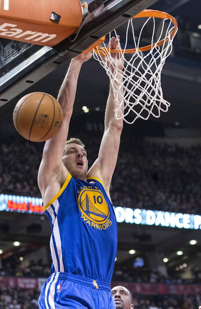 Golden State Warriors's David Lee hangs from the basket after losing possession during the first half of an NBA basketball game against the Toronto Raptors on Sunday, March 2, 2014, in Toronto