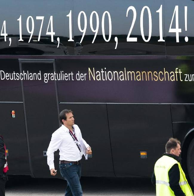 People walk in front of the team bus prior to the arrival of German national soccer team at the airport Tegel in Berlin Tuesday, July 15, 2014. Germany beat Argentina 1-0 on Sunday to win its fourth World Cup title