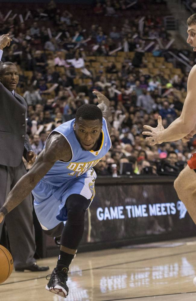 Denver Nuggets' Nate Robinson, left, drives past Toronto Raptors' Tyler Hansbrough during the second half of an NBA basketball game on Sunday, Dec. 1, 2013, in Toronto