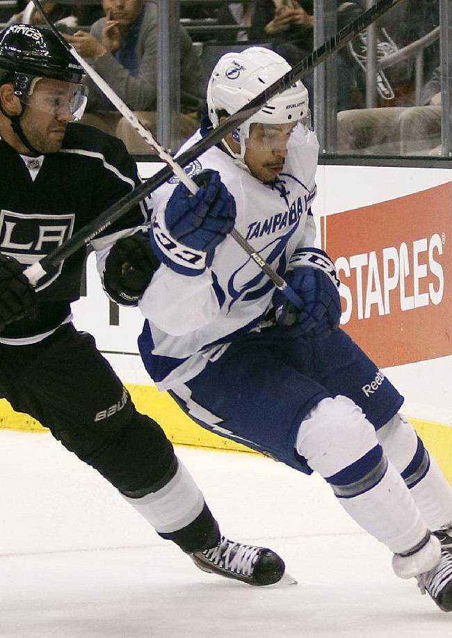 Los Angeles Kings defenseman Alec Martinez, left, battles Tampa Bay Lightning right wing J.T. Brown, right, for the puck behind the net in the third period of an NHL hockey game Tuesday, Nov. 19, 2013, in Los Angeles. The Kings won 5-2