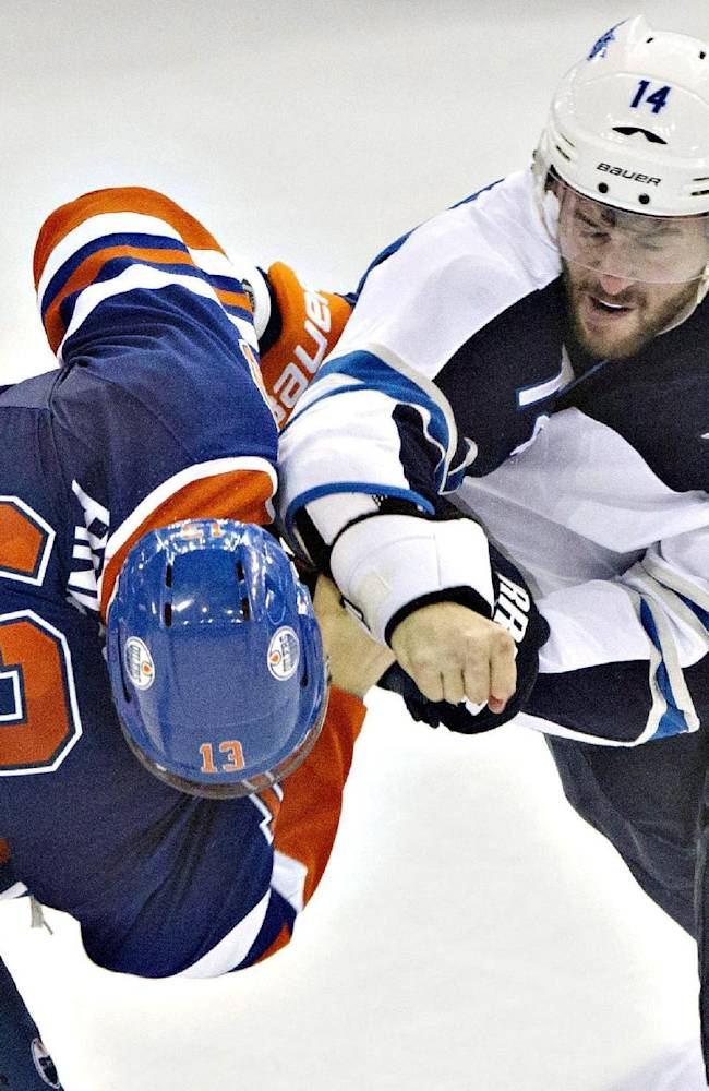 Winnipeg Jets Anthony Peluso (14) and Edmonton Oilers Steven Pinizzotto (13) fight during the third period of an NHL hockey game in Edmonton, Alberta, on Monday, Sept. 29, 2014