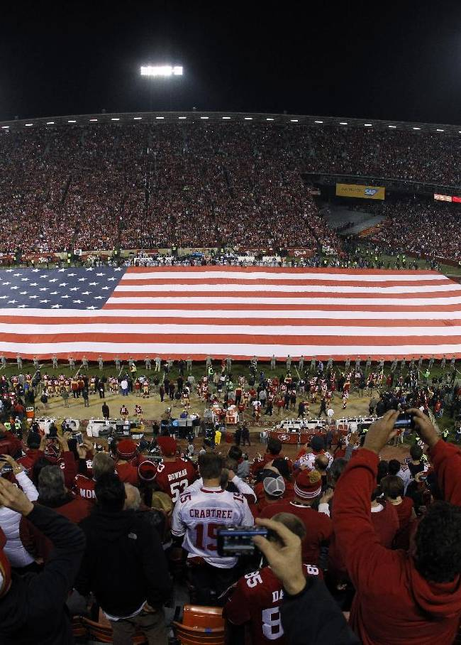 A large U.S. flag is unfurled before an NFL football game between the San Francisco 49ers and the Atlanta Falcons in San Francisco, Monday, Dec. 23, 2013. The 49ers were playing their last regular season game at Candlestick, before moving a new stadium for the 2014 season