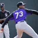 Colorado Rockies starting pitcher LaTroy Hawkins, left, watches as pitcher Jayson Aquino, right, throws during a spring training baseball practice, Friday, Feb. 21, 2014, in Scottsdale, Ariz The Associated Press