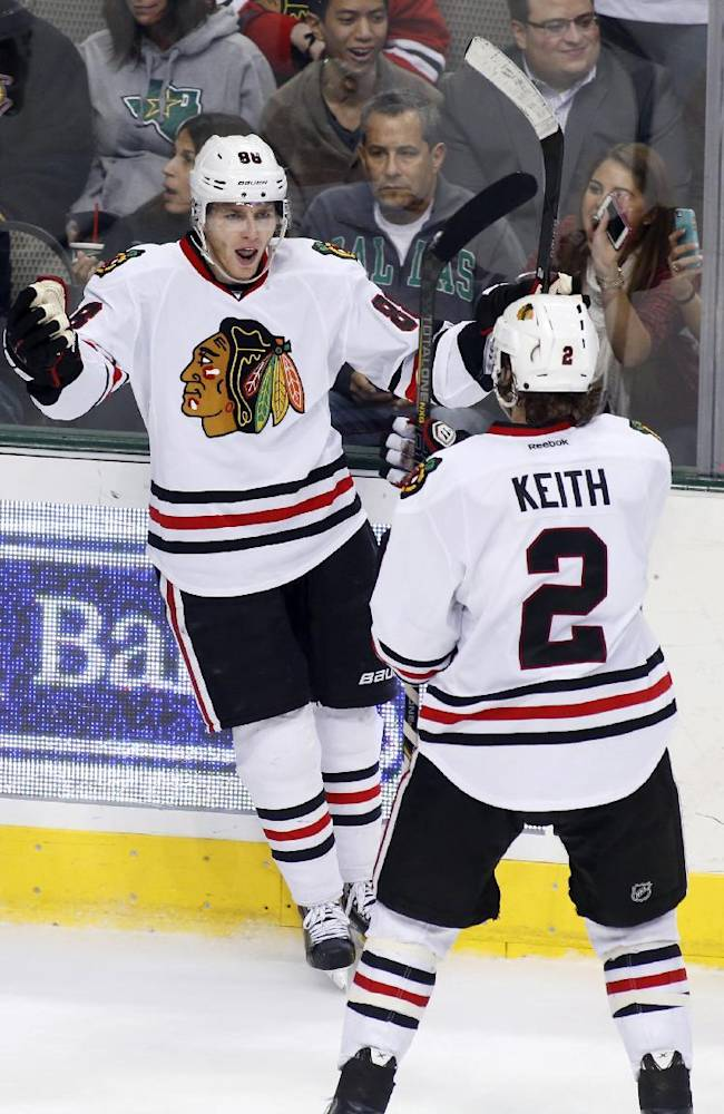 Chicago Blackhawks right wing Patrick Kane, left, celebrates his goal with defenseman Duncan Keith (2) during the second period of an NHL hockey game against the Dallas Stars, Saturday, Nov. 9, 2013, in Dallas, Texas