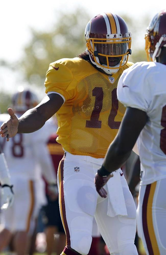 Washington Redskins quarterback Robert Griffin III (10) greets receiver Pierre Garcon after a set of drills during practice at the team's NFL football training facility, Monday, July 28, 2014 in Richmond, Va